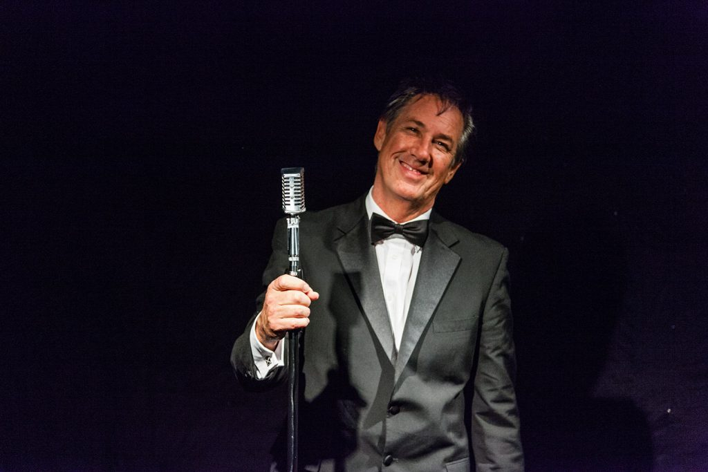 Ronnie Costley in a black tux with microphone in hand adding that touch of class to the corporate event entertainment.